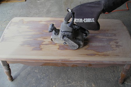 Using a belt sander to remove the finish and stain from a coffee table top.