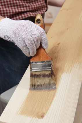 Brushing varnish on a wood plank.