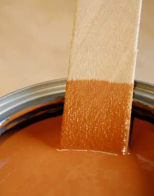 Wooden mixing stick partially submerged in new can cinnamon tinted wood stain.