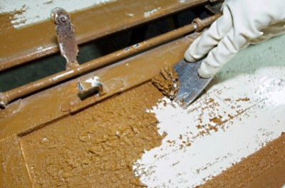 Using caustic paint stripper on an old cabinet door.